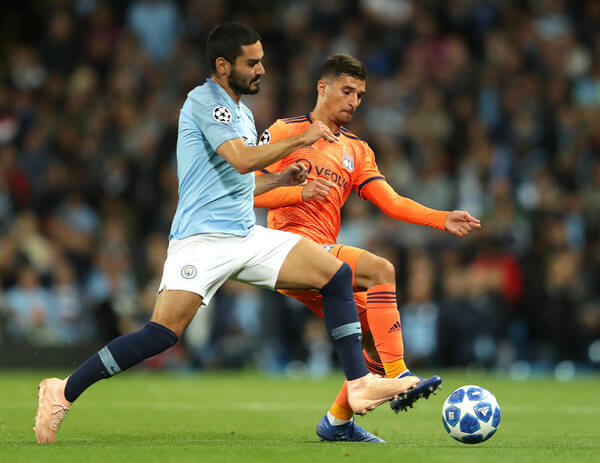 Houssem Aouar of Lyon is challenged by Ilkay Gundogan of Manchester City during the Group F match of the UEFA Champions League between Manchester City and Olympique Lyonnais at Etihad Stadium on September 19, 2018 in Manchester, United Kingdom.  (Sept. 18, 2018 - Source: Richard Heathcote/Getty Images Europe)