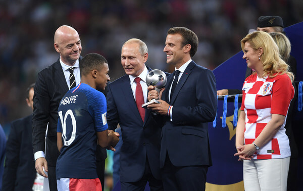French President Emmanuel Macron awards Kylian Mbappe of France with the FIFA Young Player Award as FIFA President Gianni Infantino, President of Russia Valdimir Putin and President of Croatia, Kolinda Grabar Kitarovic look on following the 2018 FIFA World Cup Final between France and Croatia at Luzhniki Stadium on July 15, 2018 in Moscow, Russia.  (July 14, 2018 - Source: Catherine Ivill/Getty Images Europe)