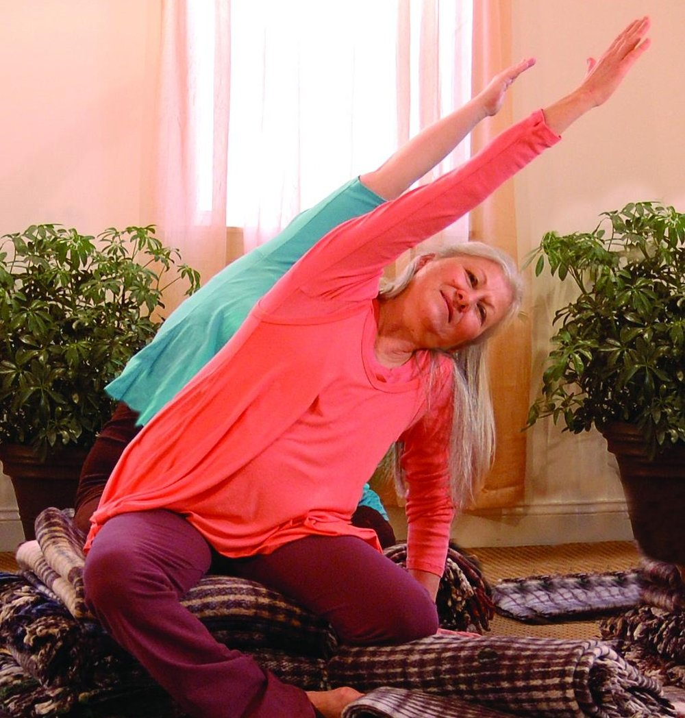 Mangala (Cayla) Allen in Seated Side Stretch pose, fully supported for an upright spine.photo used courtesy of Svaroopa® Vidya Ashram