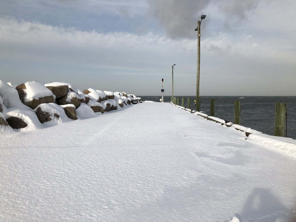 The dock at Halls Harbour, Nova Scotia  blanketed with snow.