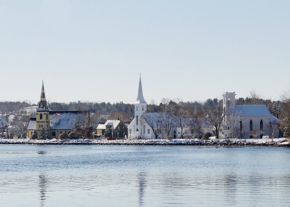 View of the Three Churches of Mahone Bay from across the harbor. - St James' Anglican; St John's Evangelical Lutheran; and Trinity United.