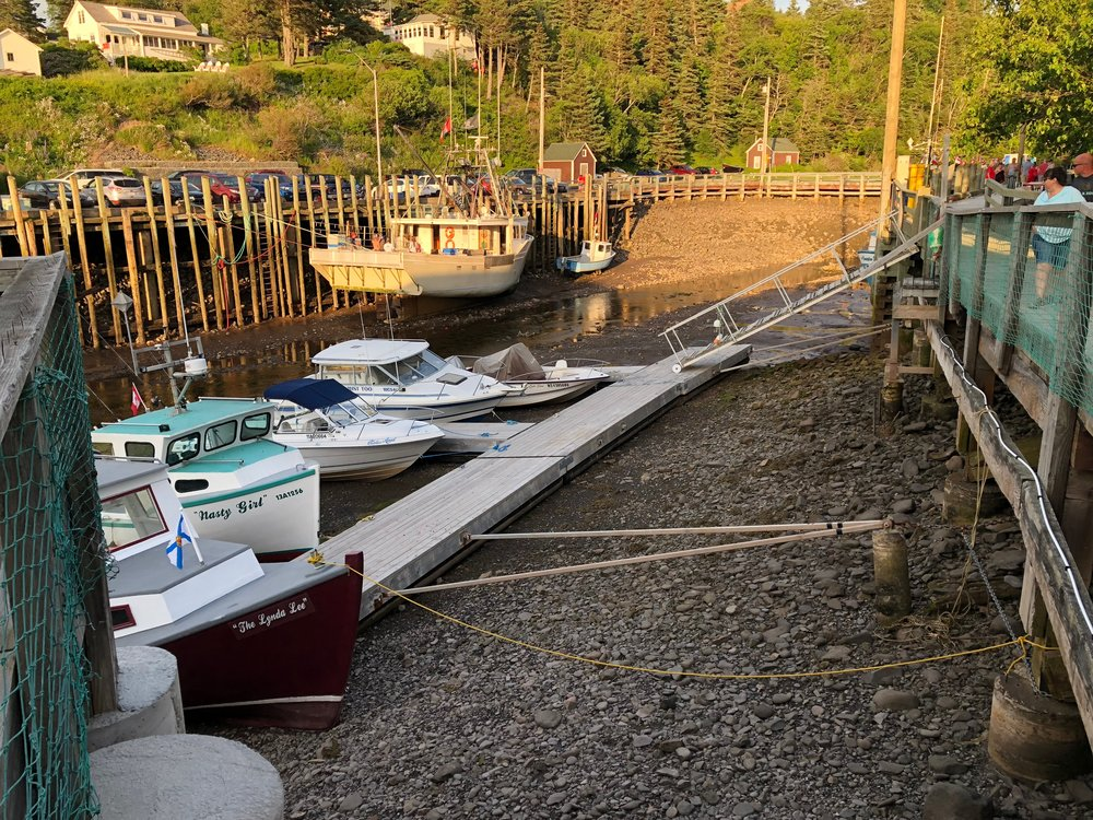Boats in Halls Harbour at low tide wait for the return of the water.