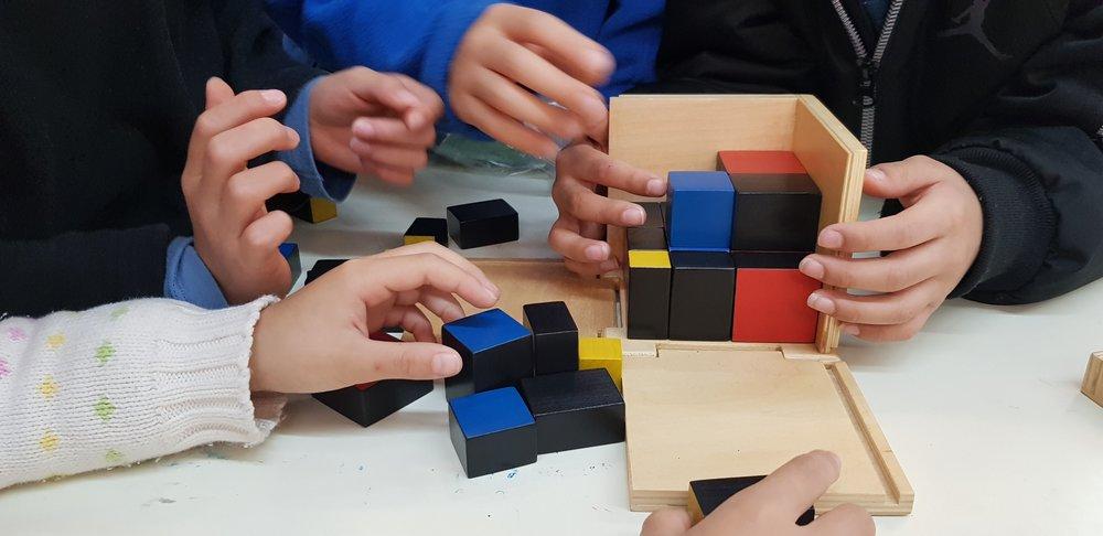 二項式   還記得讀國中時,(a+b)3 的公式嗎?這公式代表不同的邊長組合成的體積,在教室裡,打開木板側邊,利用8個木製、不同邊長的立方體方塊, 讓孩子試著不同立方體,展開二項式代數的概念,不僅培養孩子辨別大小、顏色、形狀的視覺能力,更替複雜的代數概念作預備。