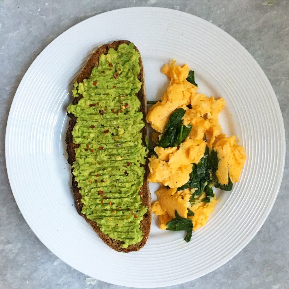 Smashed avocado on rye bread with scrambled eggs and spinach: this breakfast is a nutritional powerhouse that will fuel even the busiest of days.