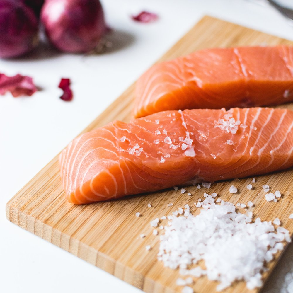 Salmon fillets on wooden chopping board