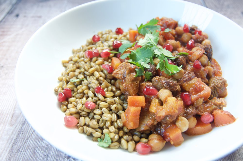 Lamb and chickpea tagine with freekeh and pomegranate in a bowl on a wooden table