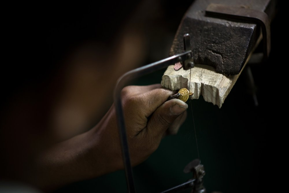 ARTISAN FILING A PIECE TO CREATE A BEAUTIFUL HANDCARFTED BUTTON
