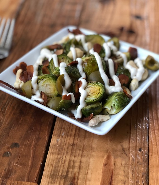 Roasted Brussels with cashew cream & coconut bacon - Tossed in a creamy cashew bath, these roasted Brussels really shine when paired with smoky coconut bacon and salty olives.