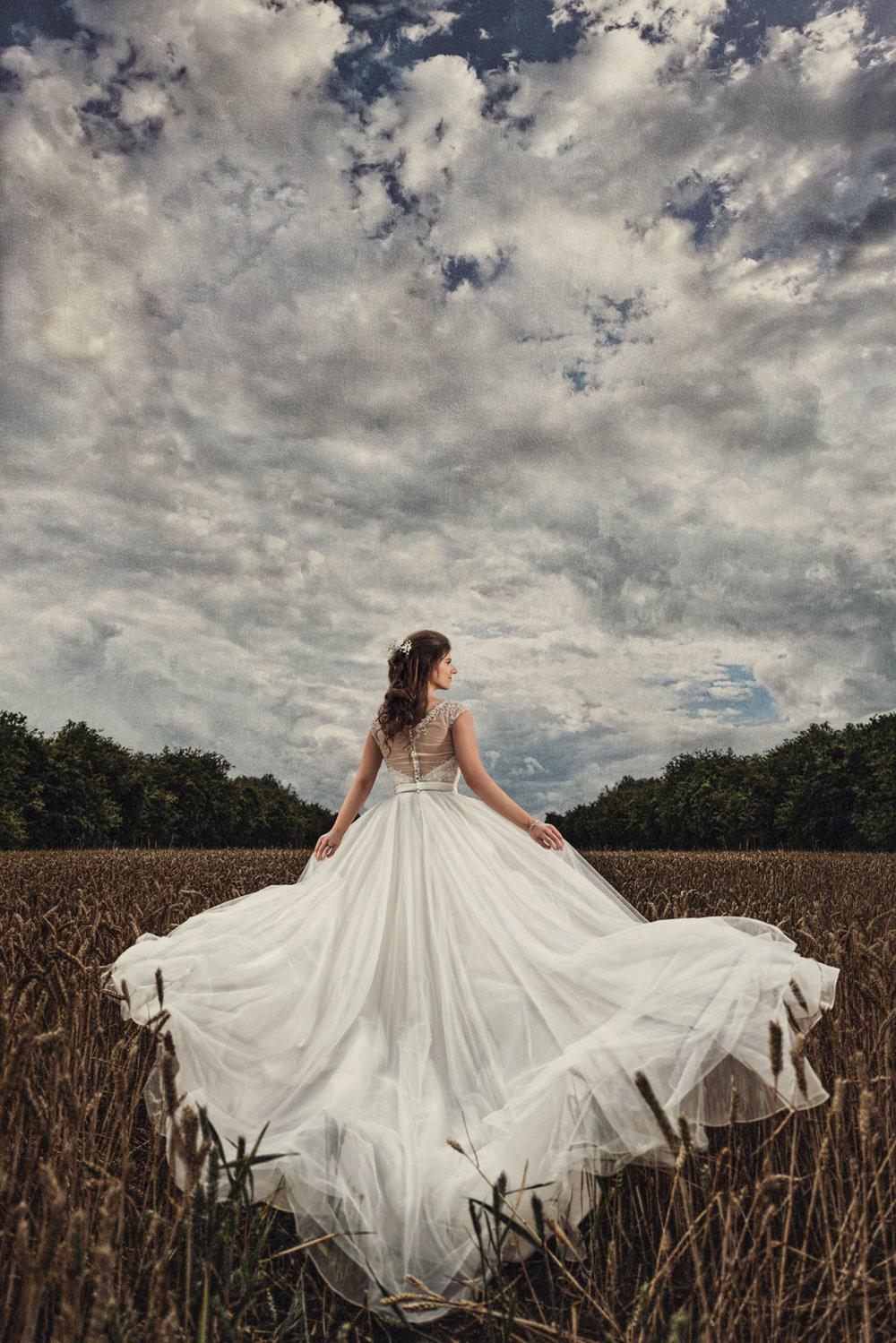 Bride walking through wheat field holding her dress
