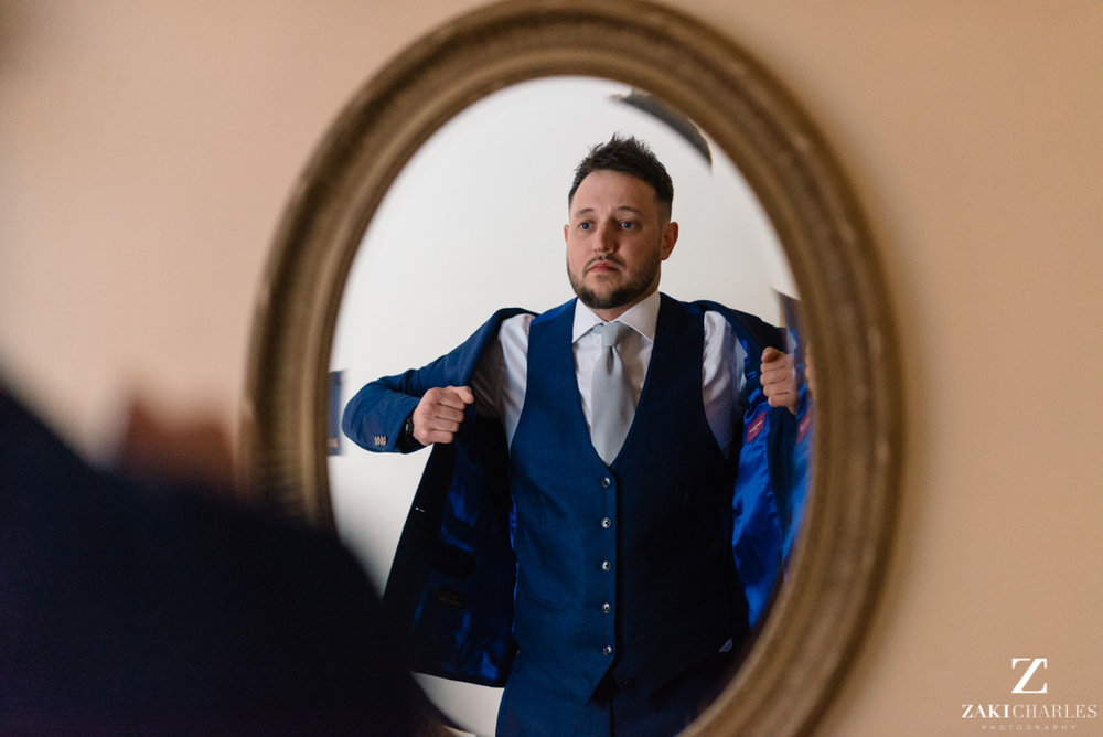 Action shot of groom putting on his jacket