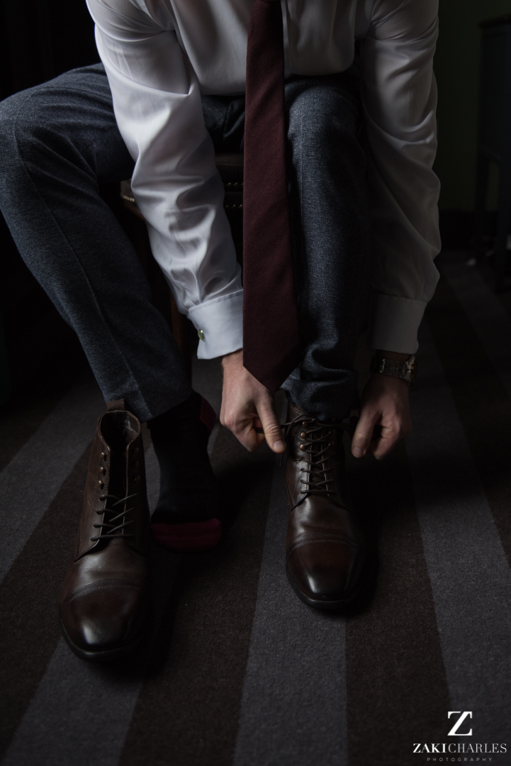 Groom tying up his shoes at the crown and thistle