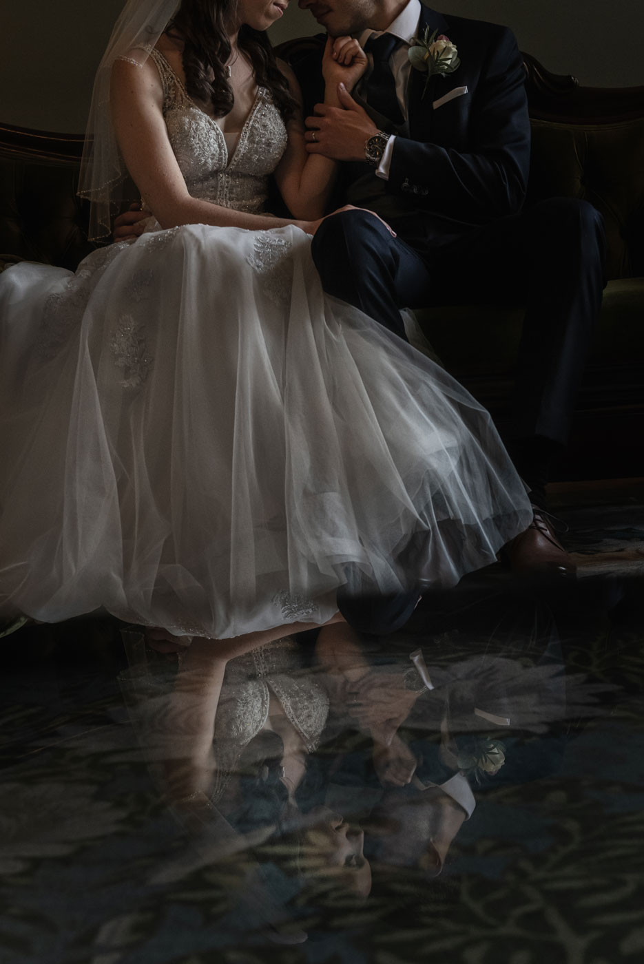 Reflection of bride and groom at Eynsham Hall