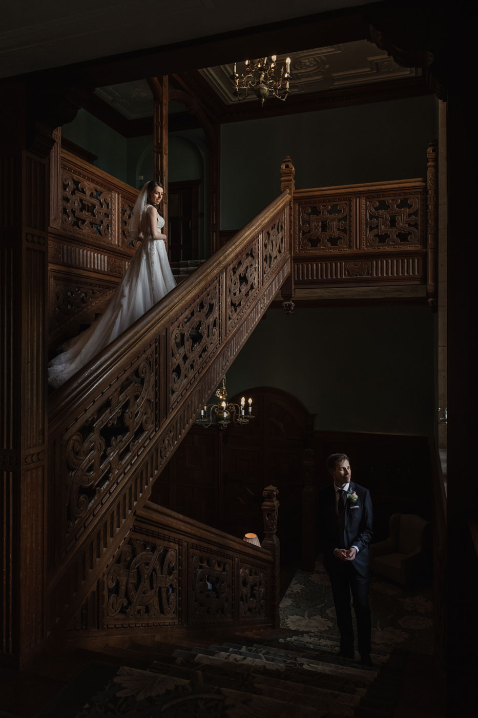 Bride and groom on stairs at Eynsham Hall