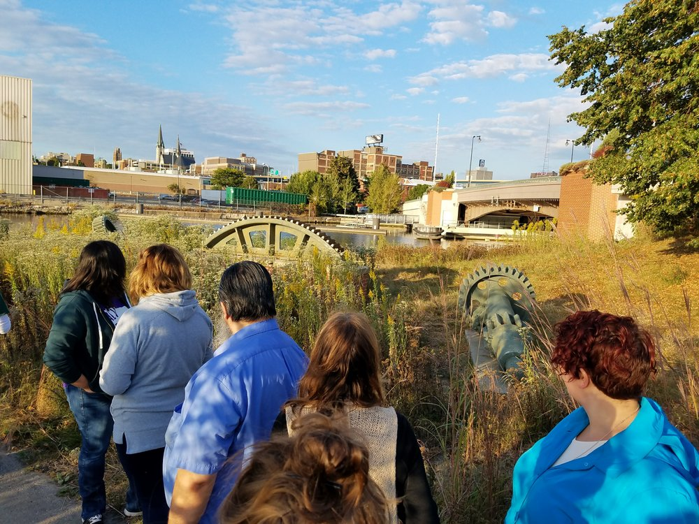 "Near ""A Place to Sit,"" Trail users can view large gears which were once used to lift the original bascule bridge that crossed Emmber Lane. The current bridge is shown in the background."
