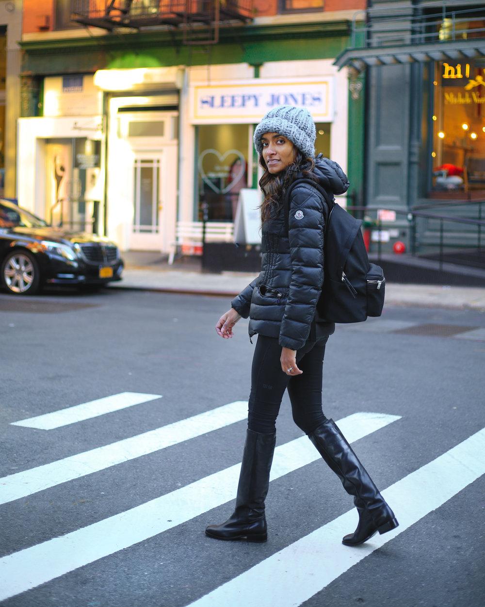 Krys posing in her black canvas Saint Laurent backpack.