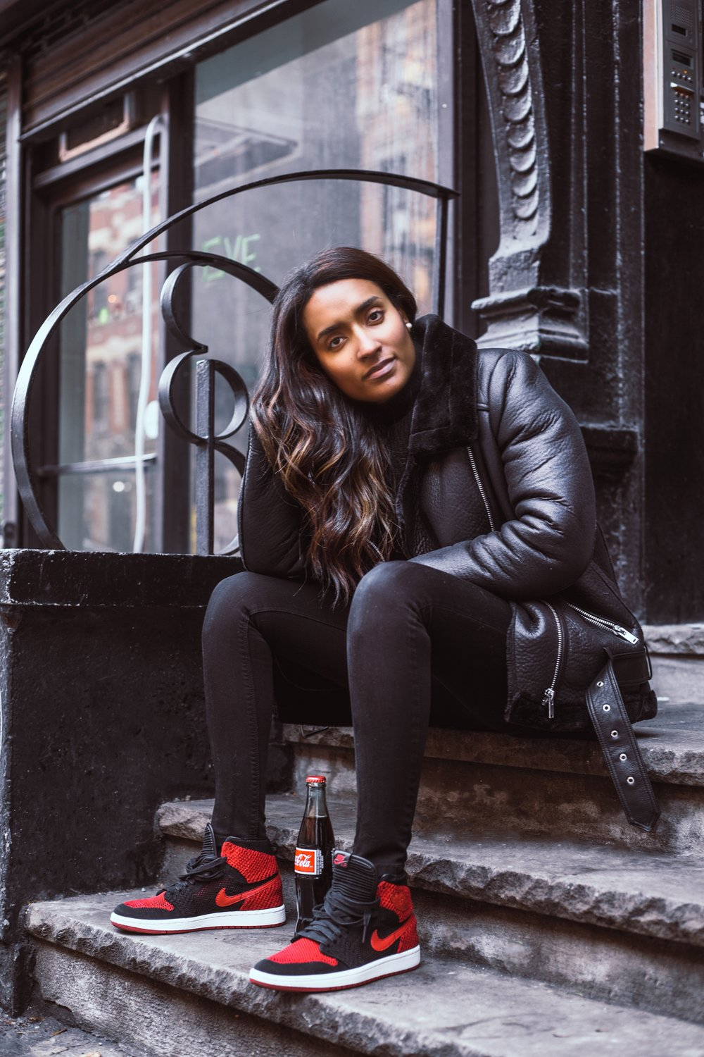 Pair of black and red Nike Air's with Coca-cola bottle on city stoop.