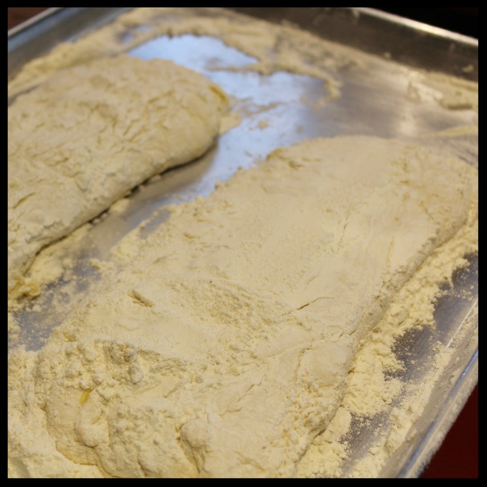 6. Heavily flour a work surface (I recommend placing the flour in a sheet pan to control the mess) and turn the risen dough onto the flour. Cut the dough in half with your scraper. Stretch each gently into a long shape, flour their bottoms well, and cover with a tea towel.  7. Preheat your oven to 500 degrees. If using a stone, also preheat at large sheet pan. If baking in cast iron preheat the pans AND lids too.  8. Once the loaves have doubled in size and are bubbly, it's time to bake them.
