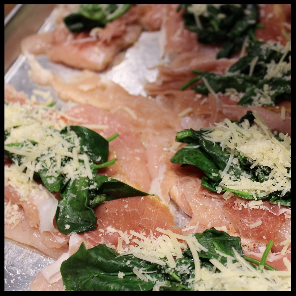 5. Top each chicken breast with a thin slice of ham or prosciutto.  6. Then add spinach, and top with parmesan cheese.