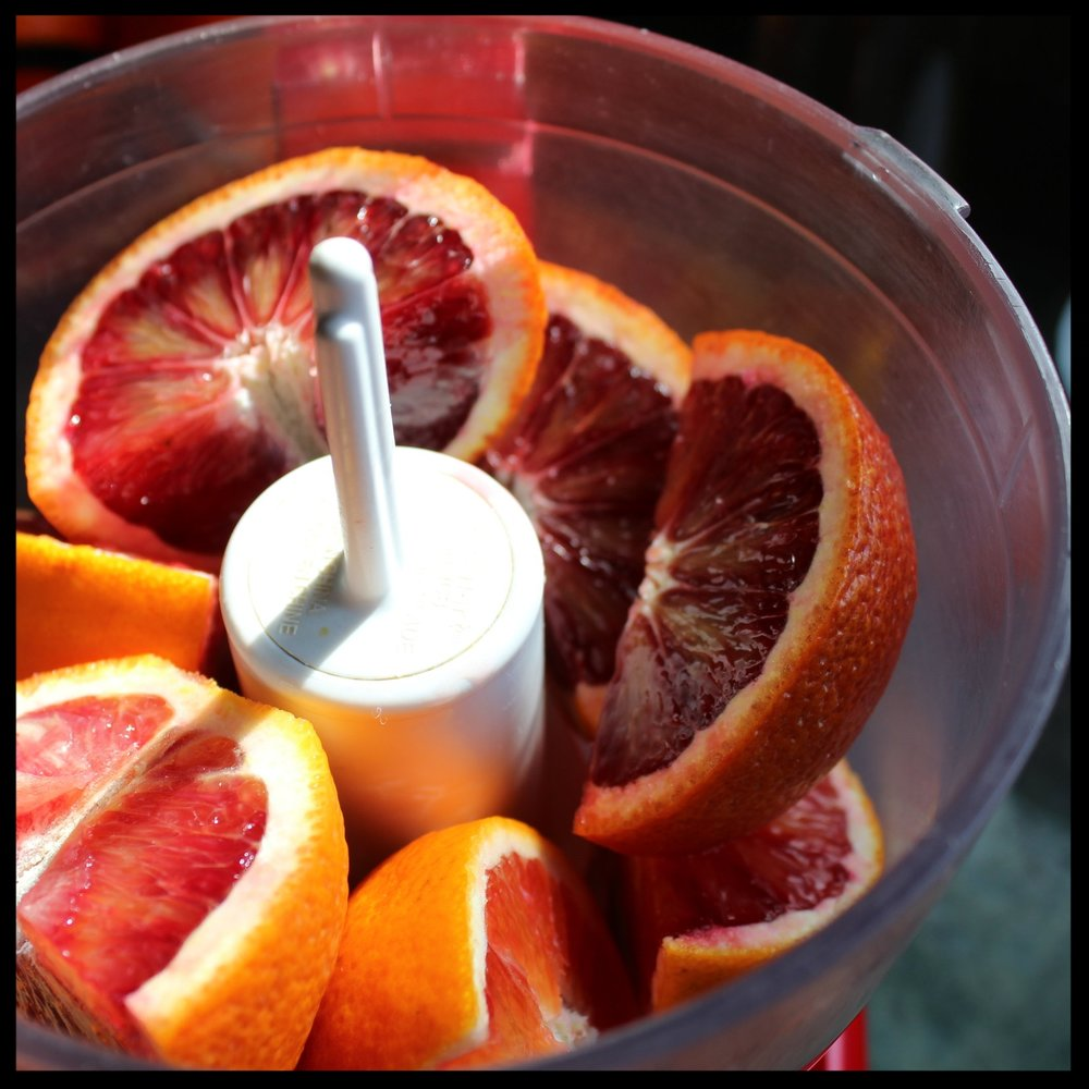 2. Put the quartered oranges into your food processor, skins and all. You may want to remove the white pithy center (it's a bit bitter).  TIP: The amazing thing about these oranges is that the pith is edible, because it's so thin. If you are using regular oranges try find those with thinner skins.
