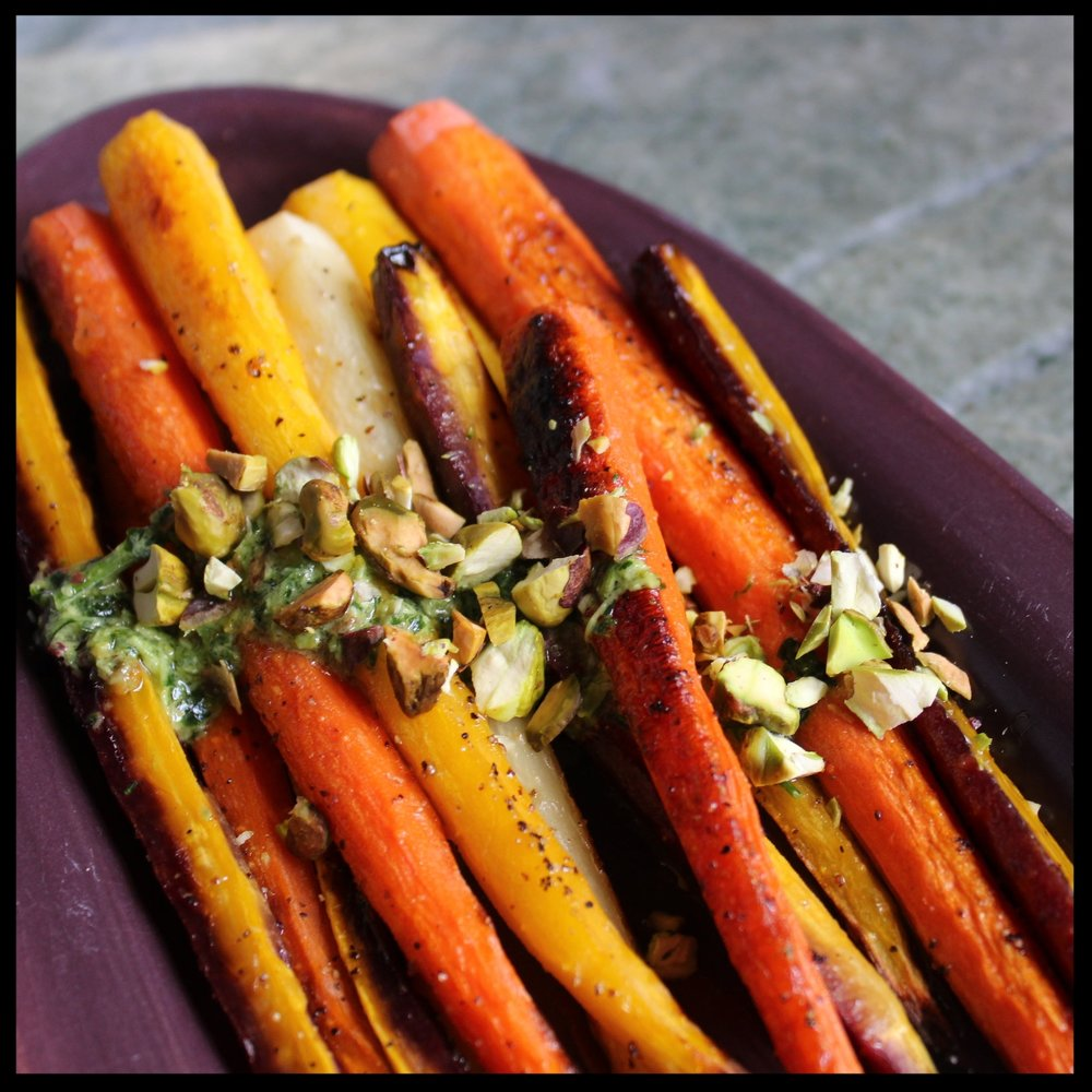 6. To serve the carrots, lay them on a colorful plate (I chose purple as it is high contrast against the yellows and oranges).  7. Drizzle the carrot top pesto over the carrots.  8. Roughly chop some of the remaining pistachios and sprinkle on top.