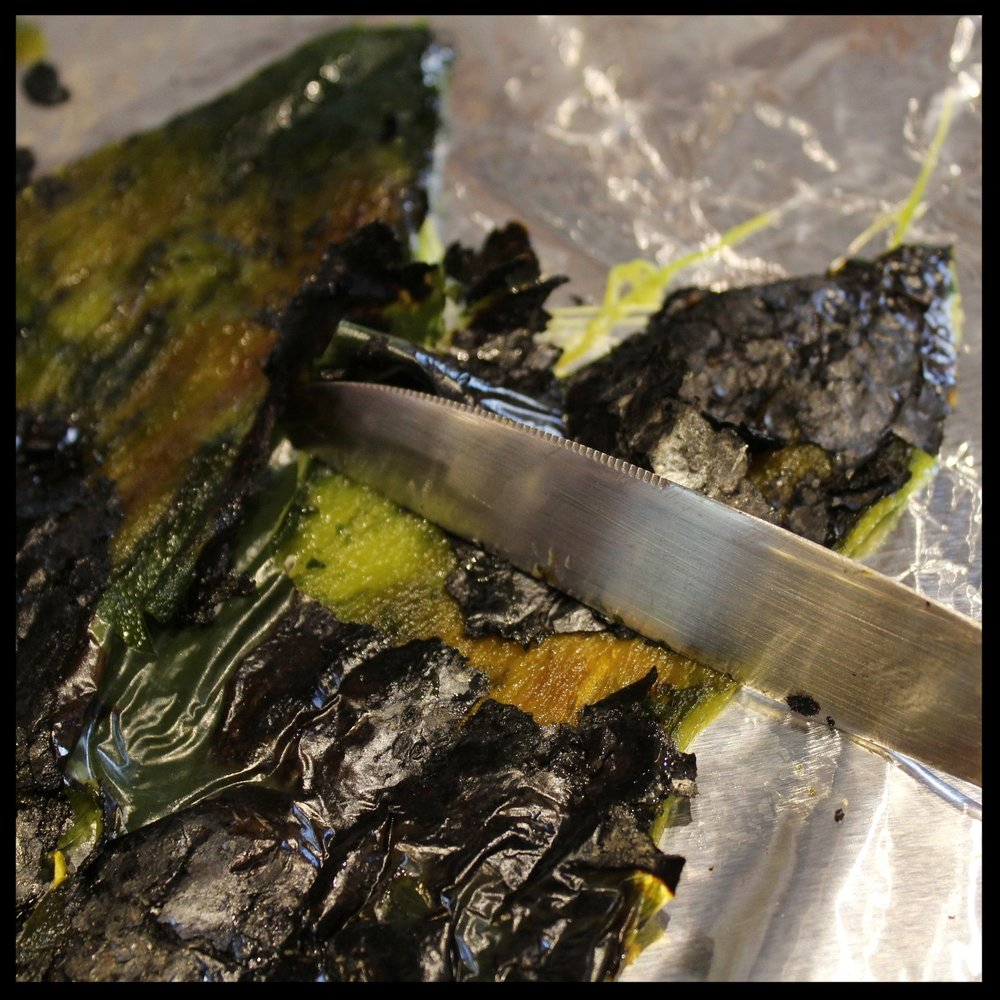 With the dull edge of the knife, gently scrape the char off the skin, onto the foil. Rotate the foil and do the same to the other half. Using the foil helps to preserve the integrity of the pepper (it less handling, less tears).