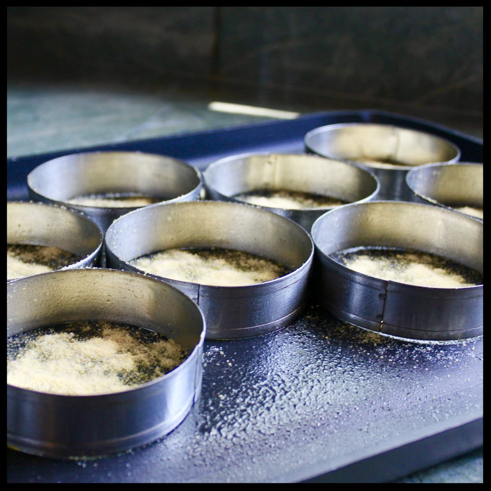 8.  Now prepare your muffin rings.  Arrange them on a griddle.  Spray the interiors with vegetable oil spray and then generously sprinkle cornmeal in the bottom.