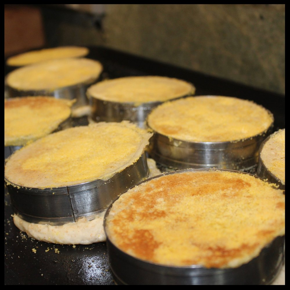 15.  Place the griddle over two burners on medium for minutes, then switch to low and let muffins cook for another 8-10 minutes.  ( Some will leak from the bottom ,as you can see above.  With the edge of a knife or bench scraper, just press firmly on the top of the ring and essentially the excess on the bottom will be cut away)  Remove those scraps.  16.  Turn the muffins over, increase heat to medium again and cook for another 5 minutes. If some of the muffins are more pale, rotate their positions on the griddle to cook evenly.