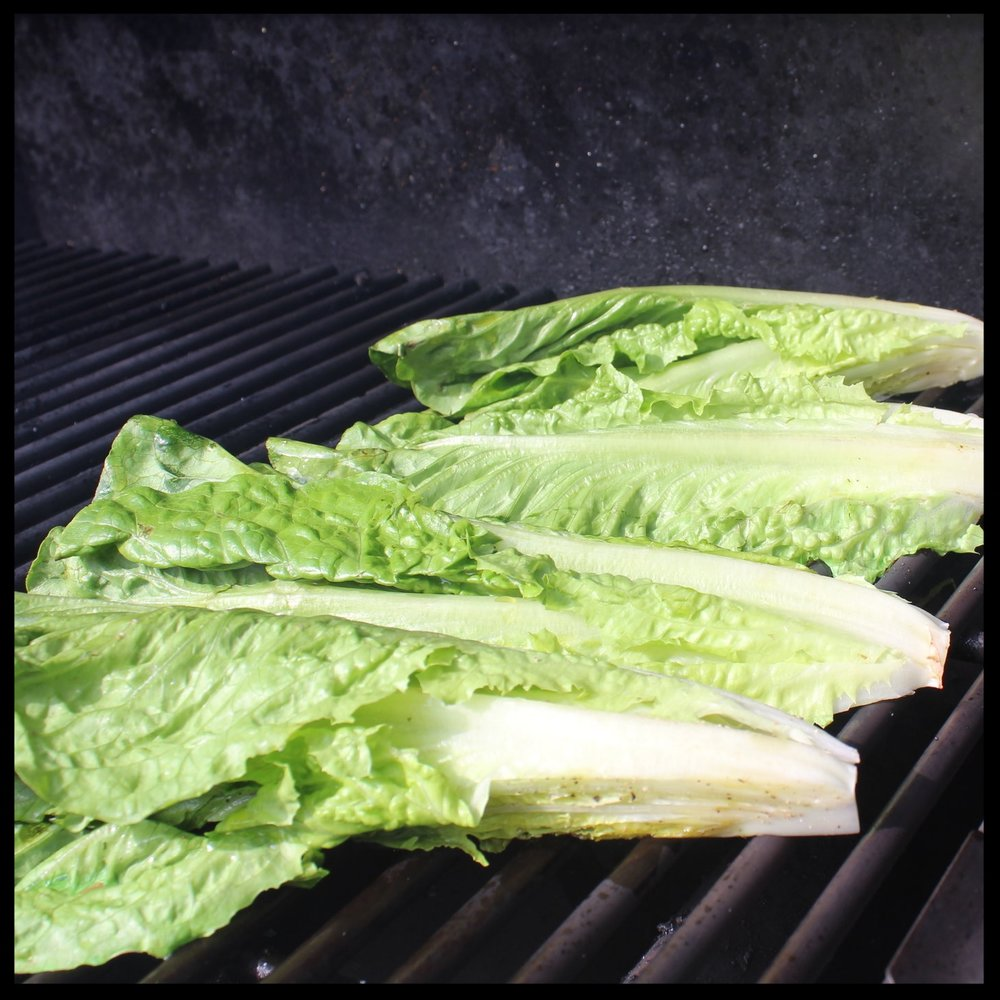 4.  Grill one side (without moving the lettuce) until edges of the leaves are charred and slightly wilted.