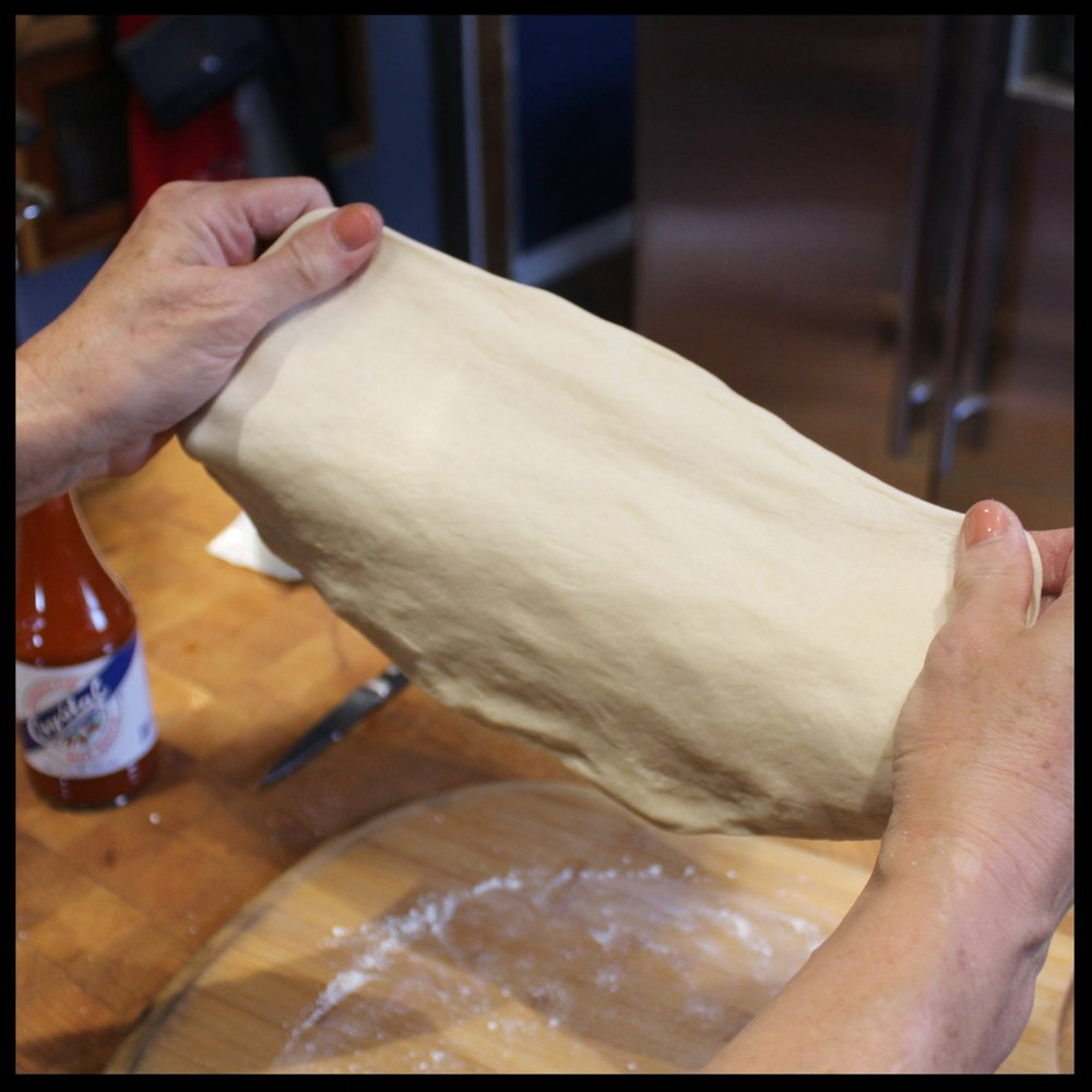 8. Now pick it up and gently stretch it (no throwing necessary) in one direction. Rotate the dough a quarter turn and repeat until you've done this 3 more times.