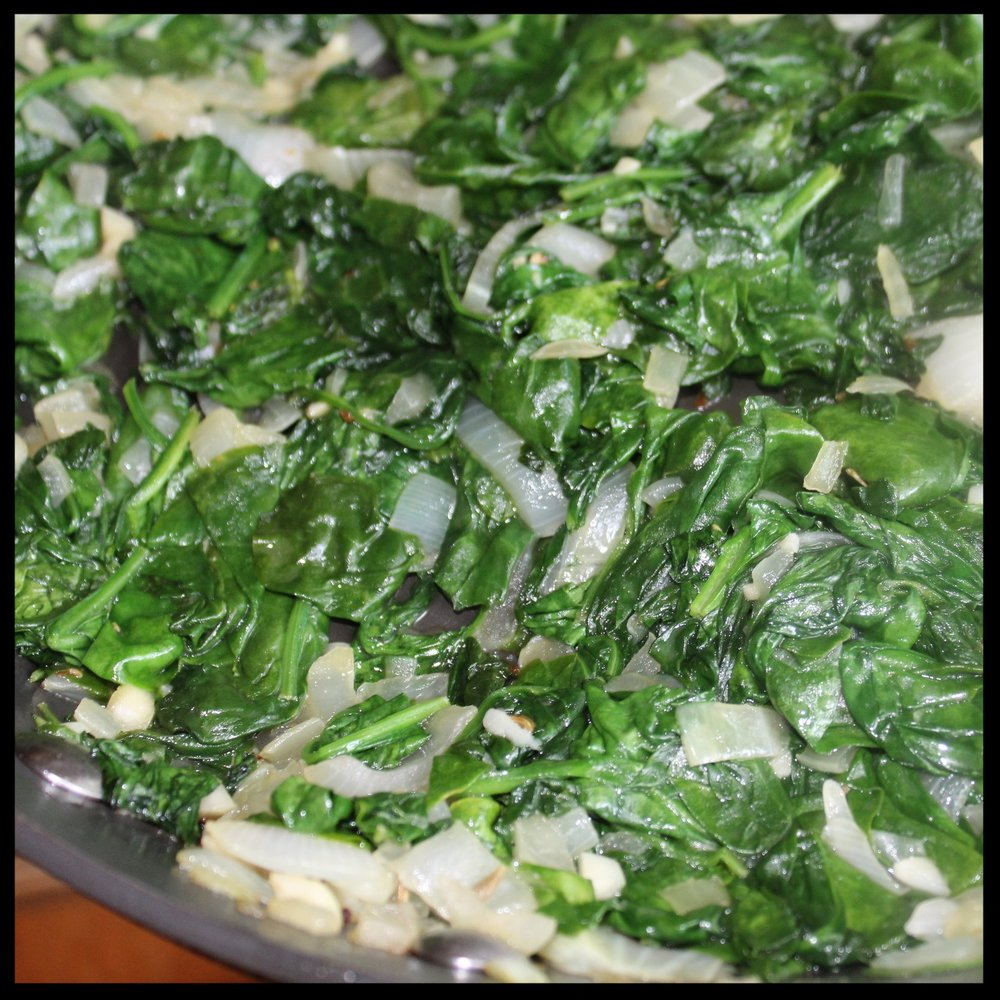3.  Add 1/2 the spinach to the pan and stir with tongs until mixed with the onions and wilted.  Add the remaining spinach and cook on medium low until spinach is very wilted and all visible moisture is gone from the pan.  4.  Take off the heat and set aside to cool a bit.  5.  Preheat the oven to 400 degrees.
