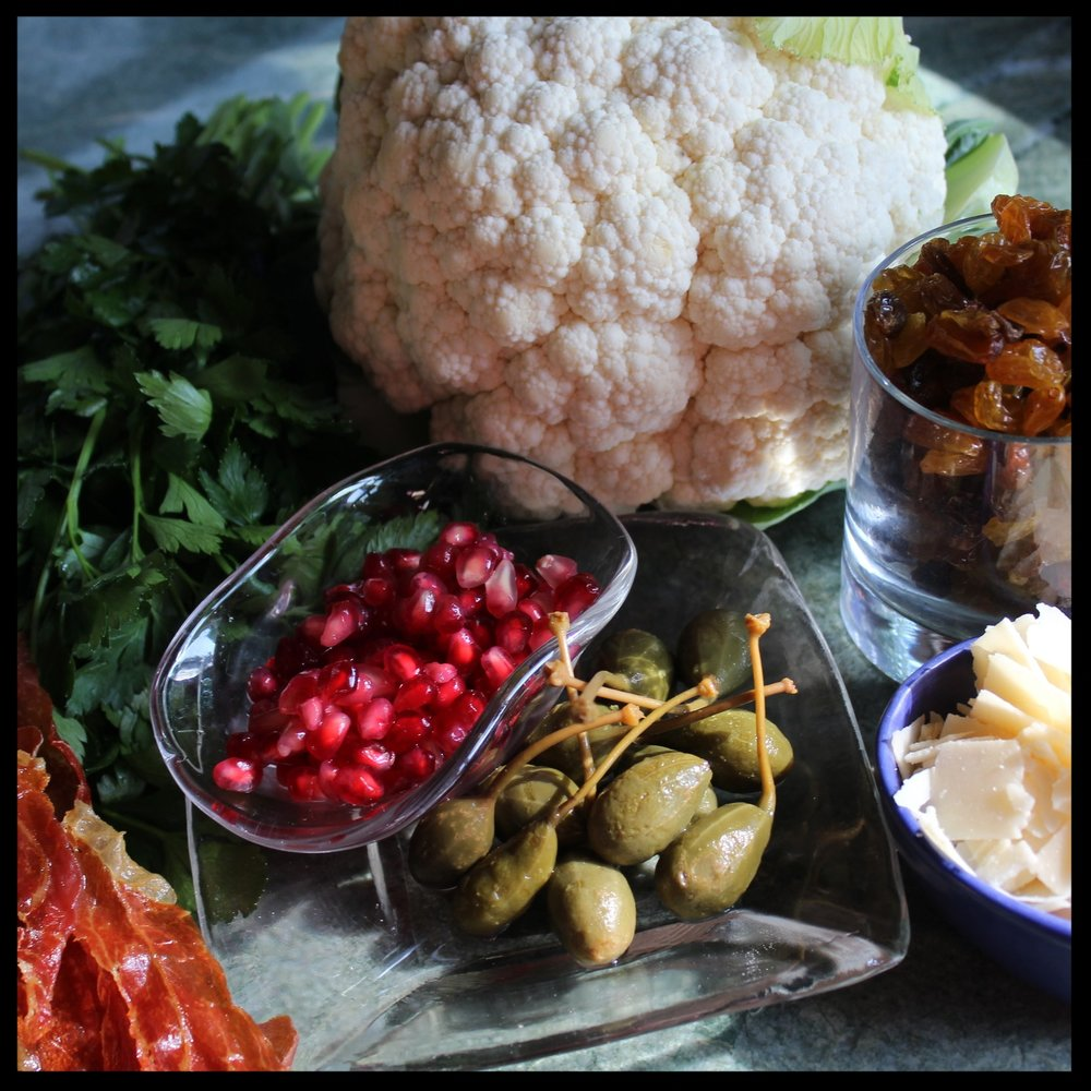 Ingredients:   2 heads cauliflower, rinsed, with large leaves snapped off  Olive oil, salt and pepper  1 jar caper berries. If salt cured, rinse and let dry. If packaged in brine, drain and pat dry.  1 cup golden raisins, soaked in water for 15 minutes and drained  Prosciutto crisps* – roughly chopped  Pomegranate seeds  1 cup parmesan  Chopped Italian parsley  1/4 cup balsamic, champagne vinegar or 2 TB lemon juice