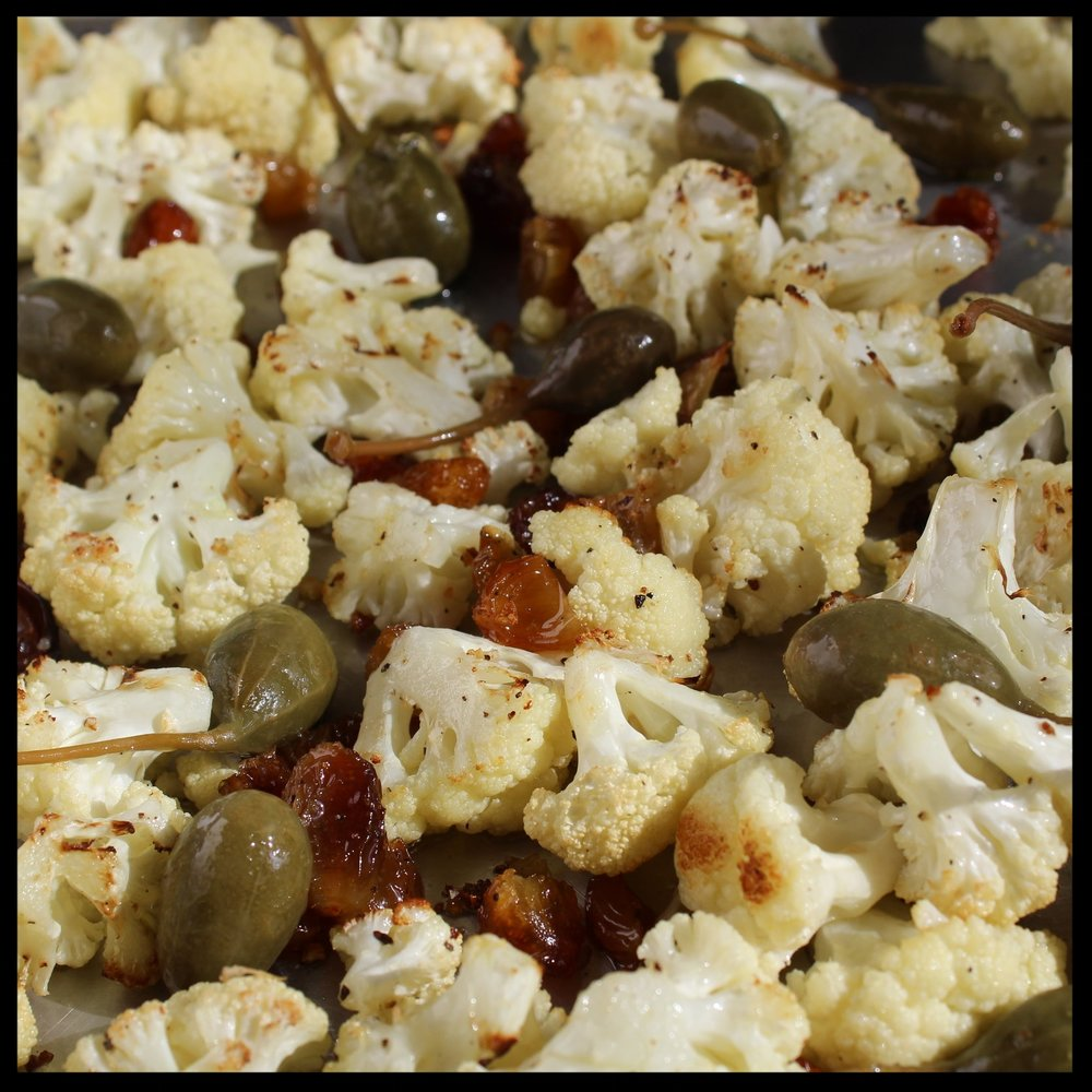 5. Roast for 15-18 minutes until browned on one side. Jostle the cauliflower with a spatula, sprinkle with the caper berries and soaked raisins, and return to the oven for another 5 minutes until cauliflower is deep golden brown, and caper berries are crispy.  6. Remove and place in a serving dish.   To serve:   Drizzle with the vinegar and top with prosciutto crisps, shards of parmesan, pomegranate seeds and freshly chopped parsley. Top with a squeeze of lemon or vinegar, and hit with a little more salt and pepper to taste.