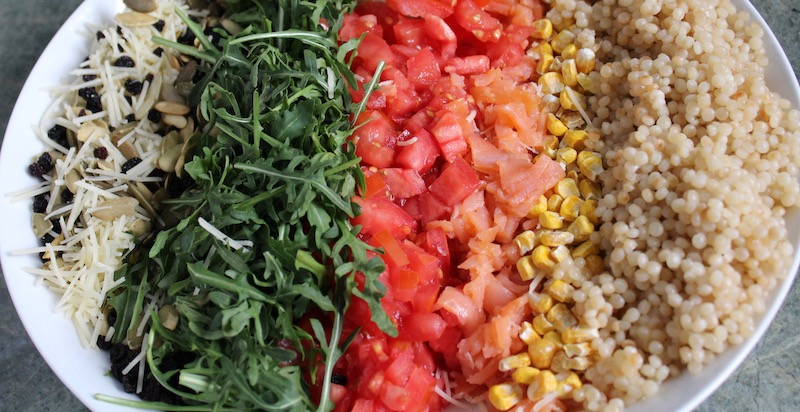 WHAT YOU NEED:  sharp knife, whisk, immersion or regular blender or food processor, measuring spoons    INGREDIENTS:    -  1 cup cooked Israeli couscous    -  1/2 cup diced Roma tomatoes    -  1/2 cup freeze-dried sweet corn    -  1 cup chopped arugula    -  2 oz smoked salmon or chicken - diced    -  1/2 cup shredded Asiago cheese (if you can't find it, use parmesan)    -  1/4 cup dried currants    -  1/4 cup toasted pepitas (pumpkin seeds)    DRESSING:    -  1/4 cup basil pesto    -  1/2 cup mayonnaise    -  1 shallot - quartered    -  1/2 cup well shaken buttermilk    -  juice of one lemon    -  salt and pepper to taste    INSTRUCTIONS:    1.  Arrange ingredients in separate rows on a large platter.      2. Put all dressing ingredients into the bowl of a food processor or blender and process until creamy and smooth. Season with salt and pepper.    3.  Pour dressing in a small pitcher and serve alongside the salad.  At the last minute, pour on the dressing and mix for the crowd.
