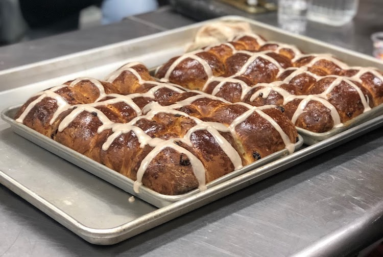 Two pans of Hot Cross Buns - iced with cardamom/cinnamon glaze