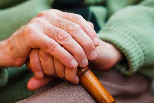 Close-up of elderly hands on a cane.