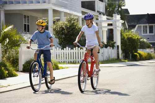 Two children riding bicycles on a street.
