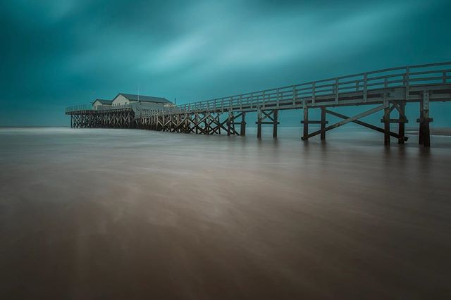 """So I just got back from an """"executive time"""" trip to Germany 😂🙈 I visited this amazing peninsula at the North Sea, with these beautiful wide beaches and fantastic structures towering up from the sand.  I got and amazing sunset the day before this shot, but as you may know, I have a style that really suits the grey skies and the moody feel of a day like on this image :) check out my site of you want to save a few $ on filters and a loupedeck :)"""