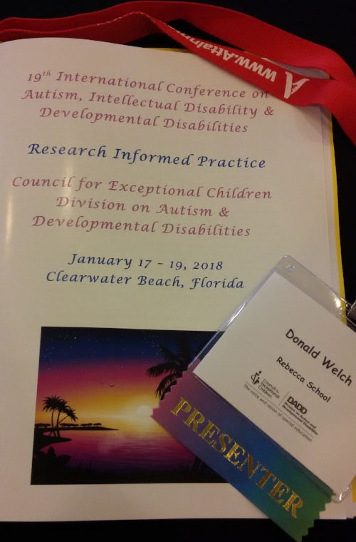 "Conference Materials for the CEC-DADD 2018 conference. At top is a red lanyard with a sponsors name on it, the name is blurred by a twist in the lanyard. Below the red lanyard is the program written in blue and pink text on a white, laminated booklet. At the bottom of the booklet is a picture of an island/beach sunset. To the right of this picture is a badge with ""Donald Welch"" on it and rainbow ""presenter"" ribbon attached."