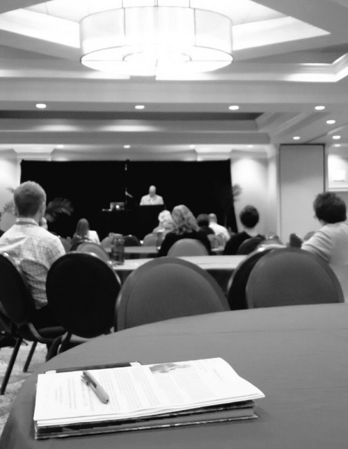 Black and white photo of a large, hotel, ballroom. In the foreground, a table with a pen and conference booklet, you can't quite make out what it says. Beyond that are people sitting in chairs at round tables and listening to a closing keynote given by an older , male caucasian speaker at a podium.