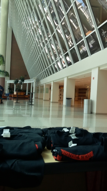 View of the National Housing Center atrium from the merch table. In the foreground, on a table, are rolled up black t-shirts with red stripes bearing black lettering. Beyond that is an atrium with tiled floors and a tall window-like structure jutting out into the atrium space.