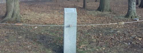 Three wooden objects suspended on a metal string, two rectangles on the left and right and in the middle a cube. A large, cement pole with indistinguishable writing is in the middle of the string behind the cube. Further in the background is a small park with trees and lawn.