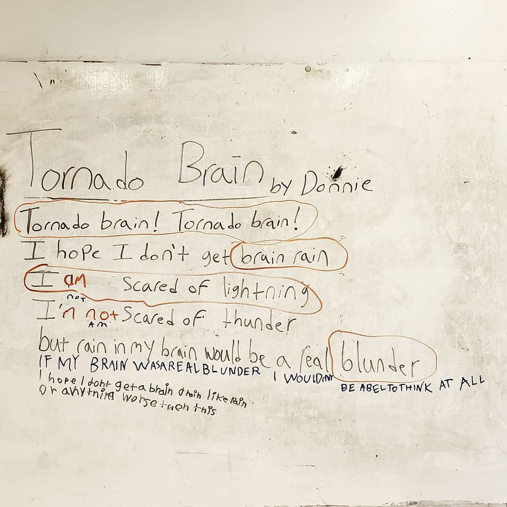 "Image of a poem written in black marker on a school white board. Photo editing has given everything a slight burnt tint. The poem's title says ""Tornado Brain"" by Donnie. Parts of the poem are circled in orange, and brown other lines have writing around them in blue and purple ink."