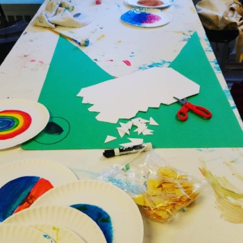 Long white table full of supplies. In the foreground are paper plates with rainbow colors, a bag of yellow cuts and a black expo marker. Next there's a green poster board cut to look like a crocodile with an eye drawn, on the green poster paper are scissors and white paper cut to look like teeth. The table extends with more rainbow plates in the background.