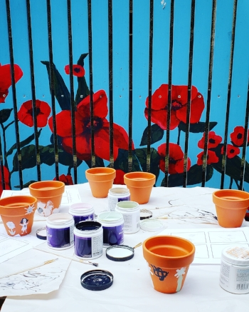 Orange/Brown ceramic pots on a white table cloth with various shades of paint in purple and white pots. Some paintings are visible on the pots, others appear blank. In the background is a vibrant teal slatted fence with red poppies painted on.