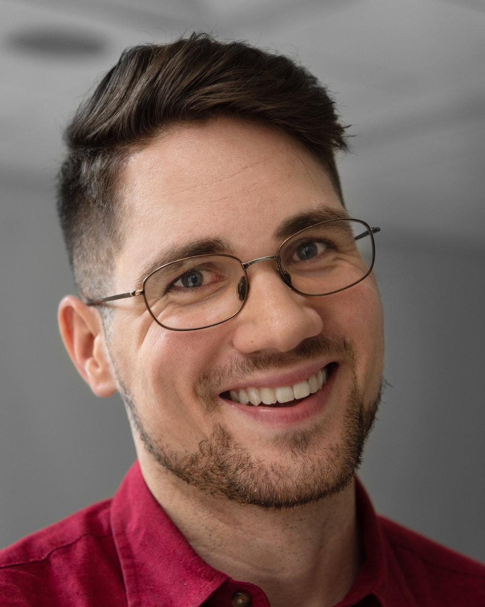 "Donnie Welch, a young white man with glasses, smiles at the camera for a head shot style photo. (This photo and ""Services"" page photo by Julie Nash)"