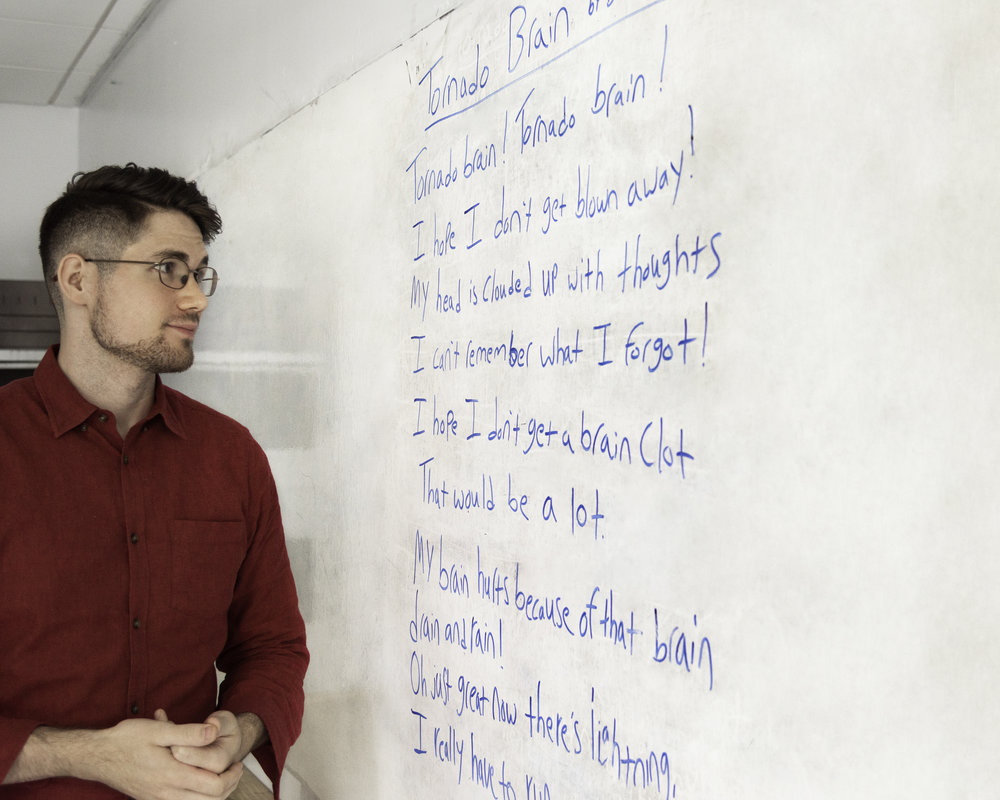 Donnie Welch, a young white man with glasses wearing a red button-down shirt, looks at a classroom white board with his hands clasped. On the board is some writing from an inclusive poetry workshop in blue expo. The angle of the photo makes it difficult to read some of the text, but it's structured in a poetic manner with line breaks.