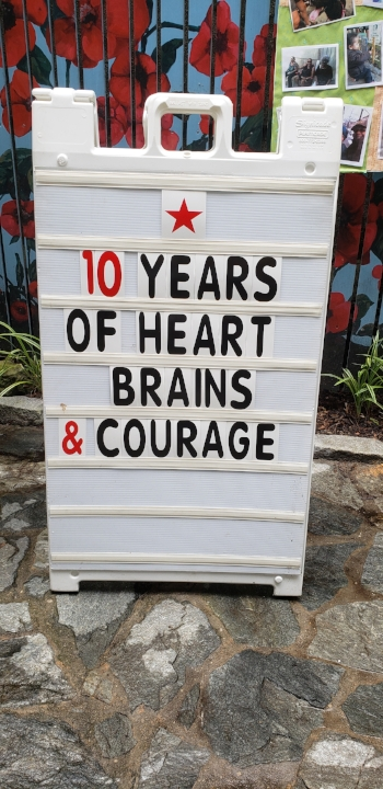 "Big white letter board sign with black and red lettering. Sign has a red star at the top and reads "" 10 years / of heart / brains / & courage"". The sign is on a rocky surface with some plants and mulch from the garden visible behind it."