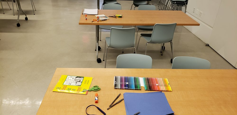 Two wooden tables with books and supplies on them. The front table has colored felt pens, blue construction paper, scissors, glue sticks, pens, and a yellow children's book. The back table has lined paper, crayons, scissors, glue, and a full length book. Both tables have gray chairs around them.