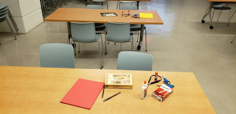 Two tables with books and supplies on them. The front table has both adaptive and regular scissors, glue, glue sticks pens, sharpies, red paper, and thick book. The back table has a children's book, yellow paper, glue, glue sticks, and scissors. Both tables have gray chairs around them.