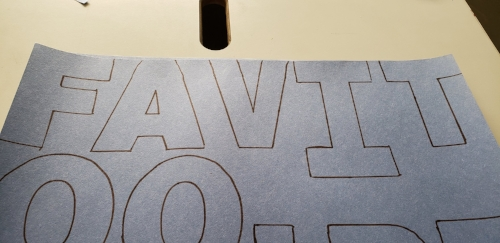 Sharpie outlines of letters on blue construction paper. The letters come to the edges of the paper.